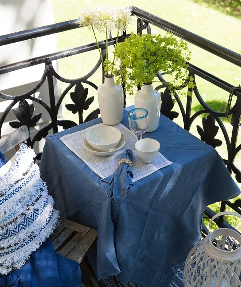 Bilde med bord og stol med pute, duk og interiør.